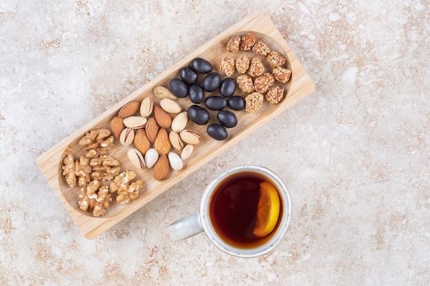 Des tas de bonbons et diverses noix dans un petit plateau à côté d'une tasse de thé