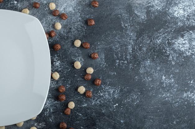 Tas de boules de céréales éparpillées autour d'une assiette blanche.