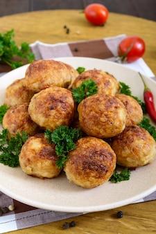 Tas de boulettes de viande dorées sur une assiette avec du persil