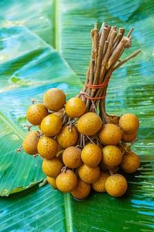 Un tas de branches de longane sur une feuille de bananier vert. vitamines, fruits, aliments sains