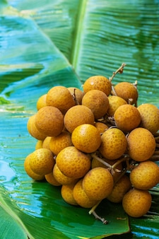 Un tas de branches de longane sur fond de feuille de bananier vert. vitamines, fruits, aliments sains
