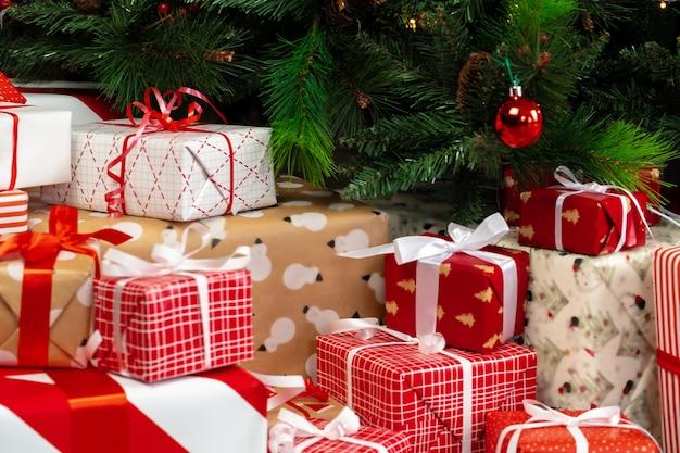 Tas de cadeaux emballés sous le sapin de noël