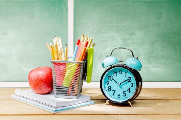 Tas de cahiers avec pomme et crayons dans un panier avec agrafeuse verte et réveil sur la table en bois