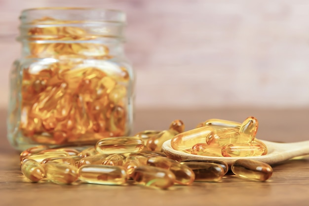 Un tas de capsule d'huile de foie de morue dans une cuillère en bois.