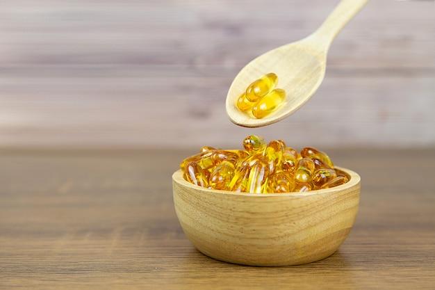Un tas de capsule d'huile de foie de morue dans une tasse et une cuillère en bois. complément alimentaire pour les concepts de soins de santé.