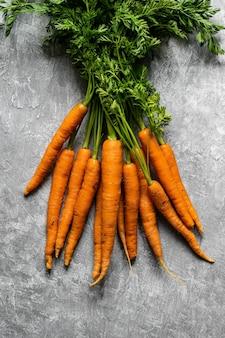 Tas de carottes biologiques fraîches sur une vue aérienne de dessus de cuisine gris