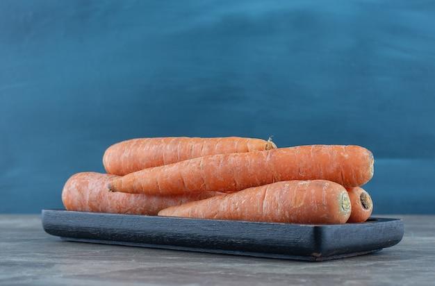 Un tas de carottes , sur la table en marbre.