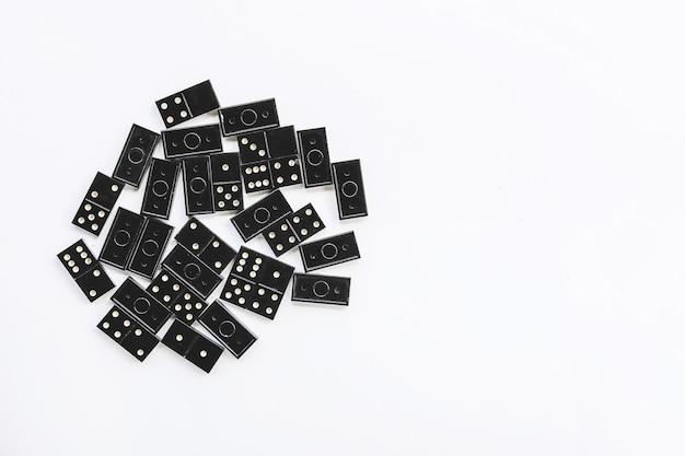 Tas de carreaux de dominos noirs vintage et de dominos dans la boîte sur fond clair.