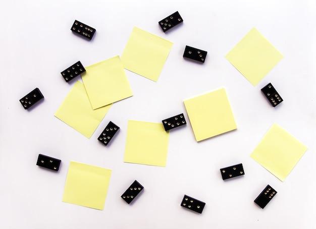 Tas de carreaux de dominos noirs vintage et de notes autocollantes sur fond clair.
