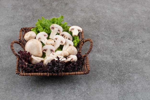 Tas de champignons sur panier avec des verts