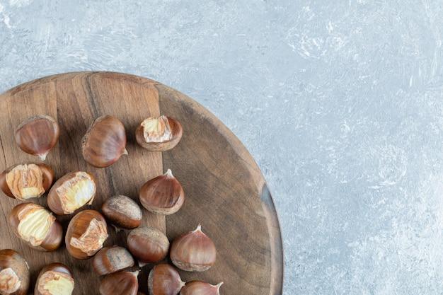 Tas de châtaignes grillées sur planche de bois.