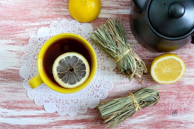 Un tas de citronnelle sèche, citron frais, théière et tasse de thé.