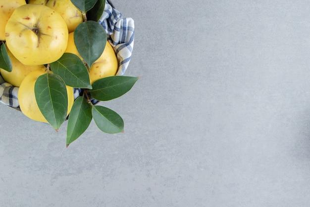 Un tas de coings et de feuilles sur marbre