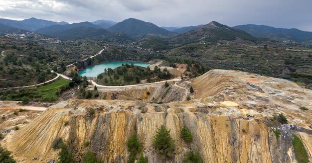Tas colorés de résidus miniers de cuivre et lac à la place de la mine abandonnée de memi à xyliatos, chypre. paysage aérien avec des montagnes lointaines