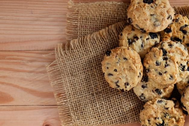 Tas de cookies aux pépites de chocolat sur le bureau en bois, vue de dessus.
