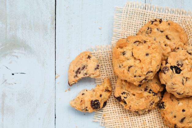 Tas de cookies aux pépites de chocolat sur le bureau en bois.
