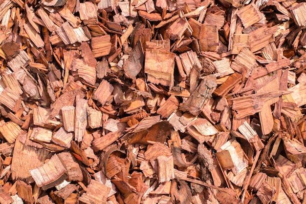 Tas de copeaux de bois rouge pour la décoration de jardin et de paysage, à l'extérieur. vue de dessus de fond bois texturé