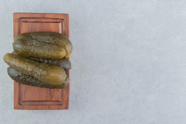 Un tas de cornichons concombre sur une planche, sur la surface en marbre
