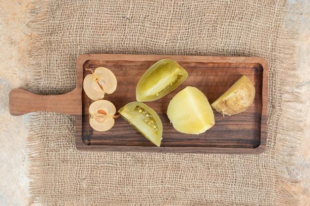 Tas de cornichons mixtes sur planche de bois.