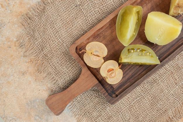 Tas de cornichons mixtes sur planche de bois