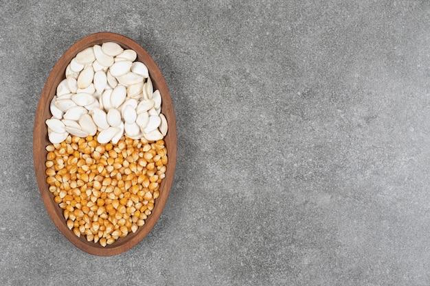 Tas de cors séchés et de graines de citrouille sur une plaque en bois.