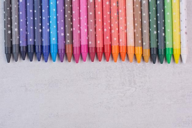 Tas de crayons colorés sur une surface blanche