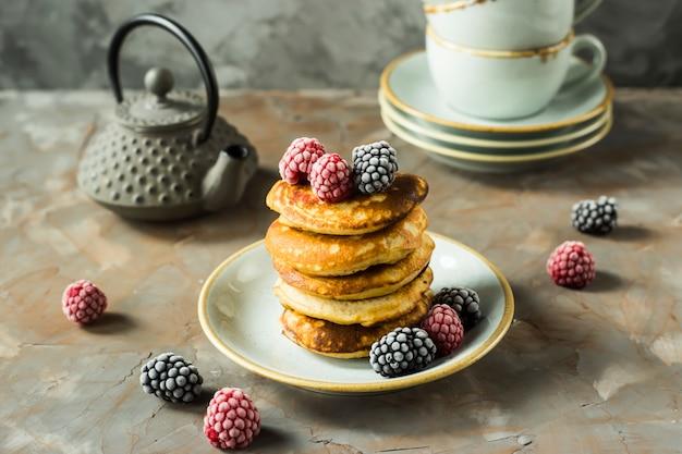 Un tas de crêpes sur une assiette avec des framboises et des mûres à côté de tasses et une bouilloire sur une table grise