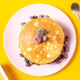 Tas de crêpes sur une assiette rose avec des mûres, des framboises et des mûres
