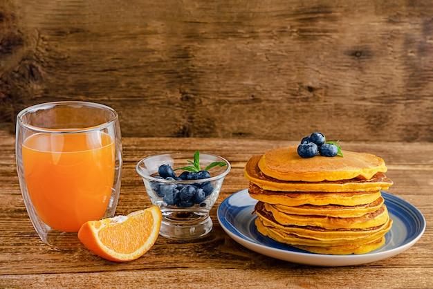 Tas de crêpes à la citrouille avec des bleuets et du jus d'orange sur une table en bois rustique. copiez l'espace.