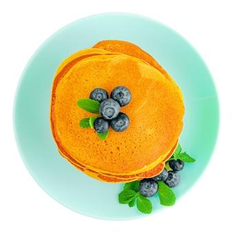 Tas de crêpes à la citrouille avec des bleuets et de la menthe sur une plaque turquoise isolé sur blanc