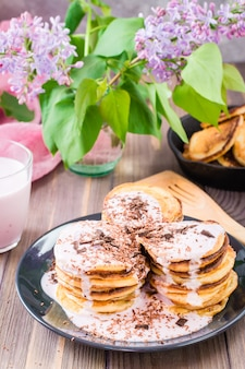 Un tas de crêpes fourrées au yaourt aux fruits et saupoudrées de chocolat râpé sur une assiette sur une table en bois