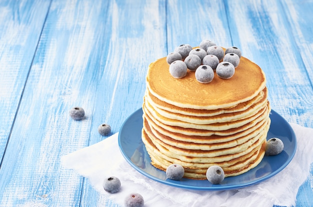 Un tas de crêpes fourrées à la myrtille congelée sur une assiette bleue sur un fond bleu saupoudré de sucre en poudre