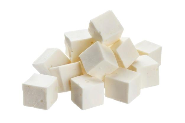Tas de cubes de feta en dés isolé sur blanc