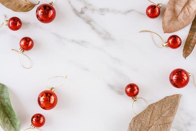 Tas de décoration de boules de noël rouge et feuilles vertes et brunes sèches sur fond de marbre blanc.