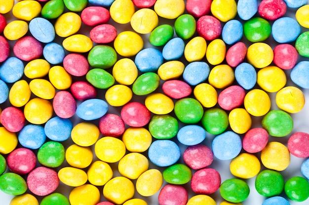 Tas de délicieux fond de bonbons de chocolat coloré arc-en-ciel