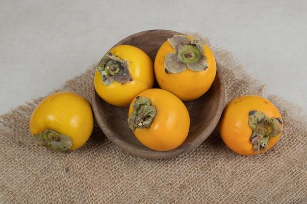 Tas de délicieux kakis mûrs dans un bol en bois