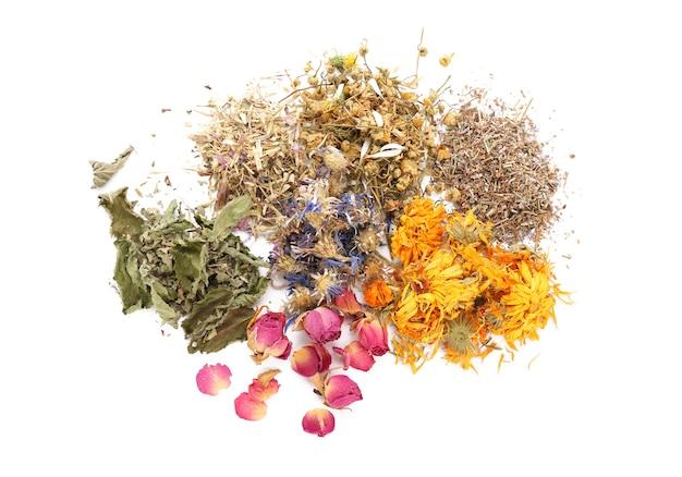 Tas de différentes herbes et fleurs séchées aromatiques sur fond blanc