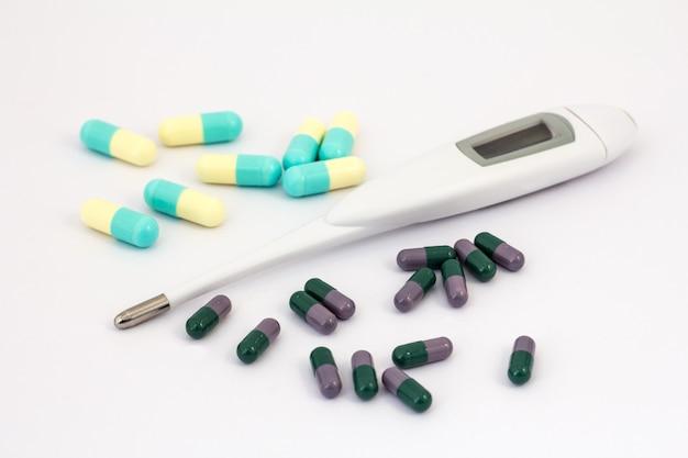 Tas de différentes pilules et thermomètre numérique sur fond blanc. cupcules vert foncé et lilas, jaune clair et bleu