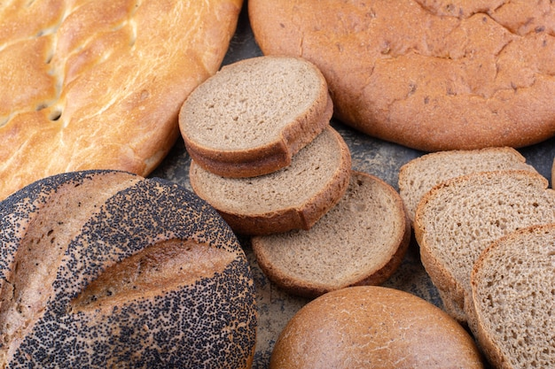 Tas de différents types de pain se regroupent sur une surface en marbre