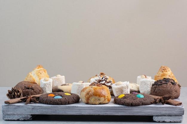 Tas de divers biscuits sur planche de bois avec des pommes de pin. photo de haute qualité