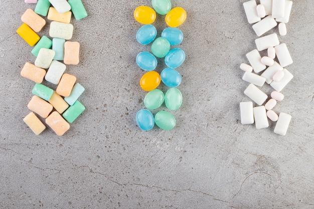 Tas de divers chewing-gums placés sur une table en pierre.