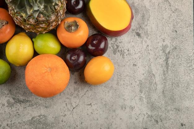 Tas de divers délicieux fruits frais sur une surface en marbre.