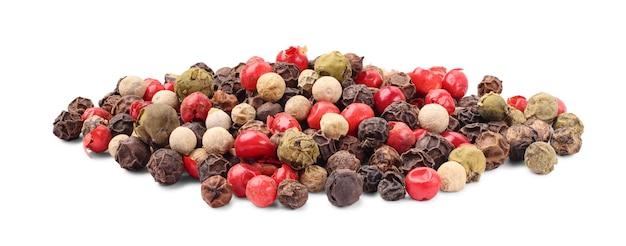 Tas de divers grains de poivre isolé sur fond blanc. mélange de grains de poivre séchés noir, blanc, vert et rouge, gros plan. vue de dessus.