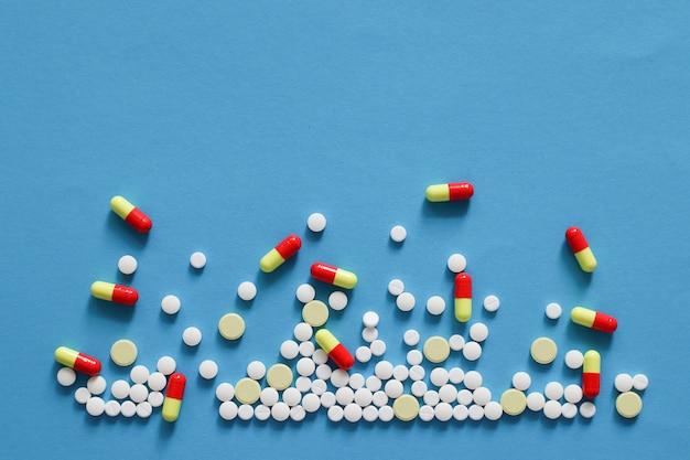 Tas de diverses pilules isolées sur fond bleu.