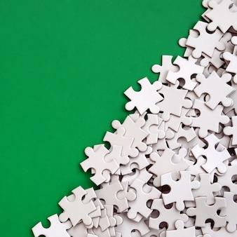 Un tas d'éléments non peignés d'un puzzle blanc repose sur le fond d'une surface verte.
