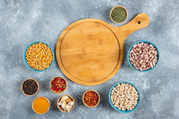 Tas d'épices et bols de haricots, cors autour d'une planche de bois.