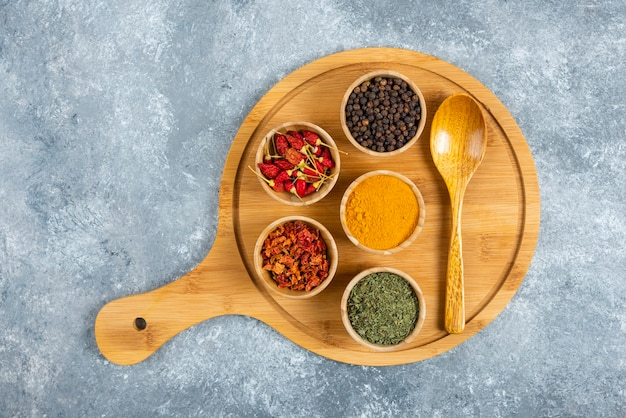 Tas d'épices avec cuillère sur planche de bois.