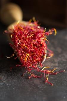 Un tas de ficelle de safran rouge vibrant sur une cuillère en bois sur une surface sombre