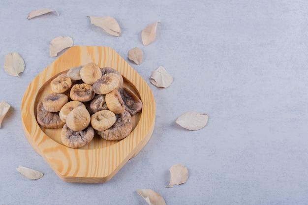 Tas de figues séchées sucrées placées sur une plaque en bois avec des feuilles.