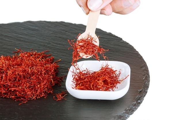 Tas de fils de safran secs sur un fond texturé noir. pimenter. l'utilisation du safran en médecine, cuisine, cosmétologie.